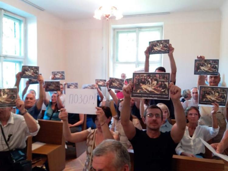 """В суде Бреста люди развернули плакаты с копией картины """"Сдирание кожи с продажного судьи"""""""