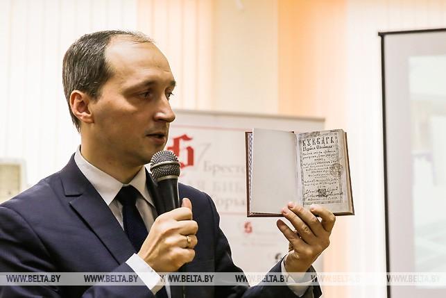 Заместитель директора Национальной библиотеки Беларуси Александр Суша держит в руках факсимильное издание