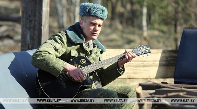 Гвардии сержант Владислав Левицкий играет на гитаре во время дня открытых дверей на полигоне